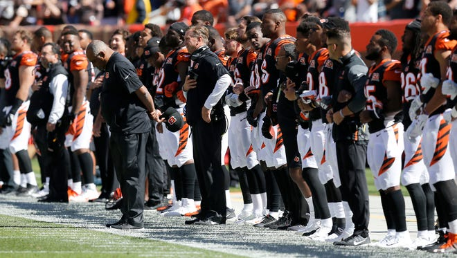 The Cincinnati Bengals sideline likes arms for the national anthem before the first quarter of the NFL Week 4 game between the Cleveland Browns and the Cincinnati Bengals at FirstEnergy Stadium in downtown Cleveland on Sunday, Oct. 1, 2017. At halftime, the Bengals led 21-0.