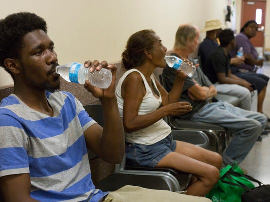 Maceo Jackson, 23, and Maria Moreno, 58, drink water that's handed to them as they wait in line to work with the Homeless ID Project on June 6, 2018, in Phoenix, Arizona.