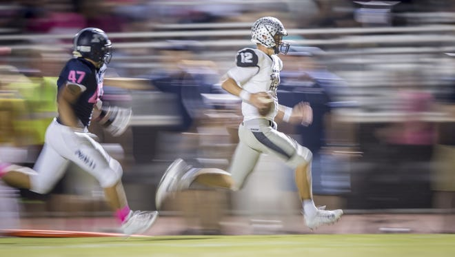 Hamilton quarterback Tyler Shough (12) runs the ball in the first half of the high school football game between the Perry Pumas and the Hamilton Huskies at Perry High School on Friday, October 20, 2017 in Gilbert, Arizona.