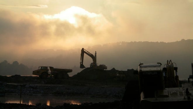 A cloud of coal ash depicted above the cleanup site.