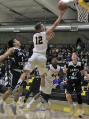 Alamogordo's Jason Campbell extends out his arm during a layup attempt Friday night.