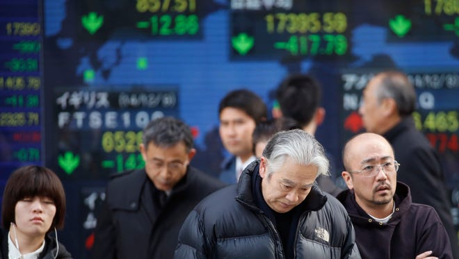 People cross a street in front of an electronic stock indicator of a securities firm in Tokyo on Dec. 10.