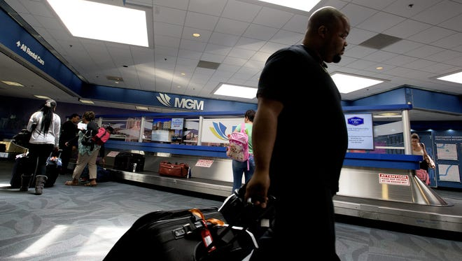 Passengers pick up luggage after arriving at the Montgomery Regional Airport in Montgomery, Ala. on Wednesday August 12, 2015.