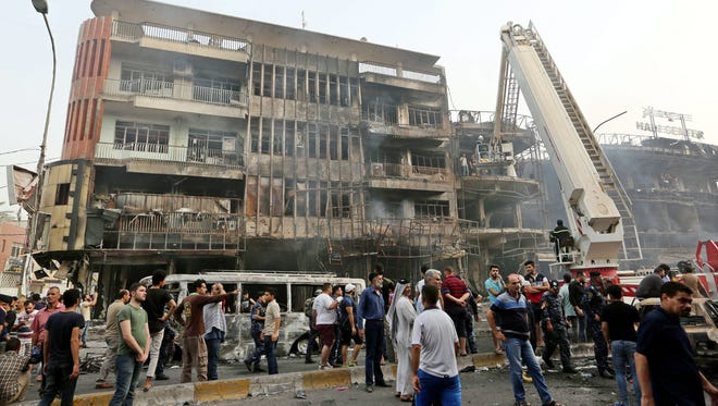 Iraqis gather at the site of suicide car bomb attack in the Karada district of central Baghdad, Iraq, on July 3, 2016.