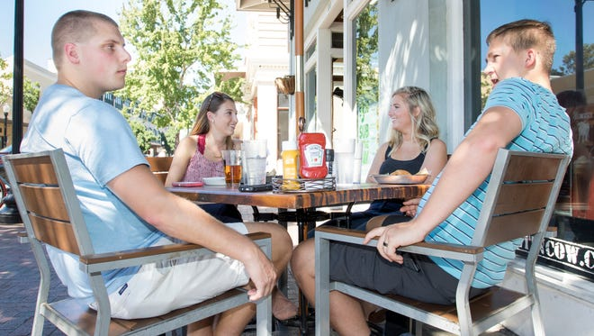 Luke and Paige Hinkle, left, of Pensacola, have lunch with Jacksonville guests Megan and Grant Goschenour on Palafox Street in Pensacola on Oct. 7.