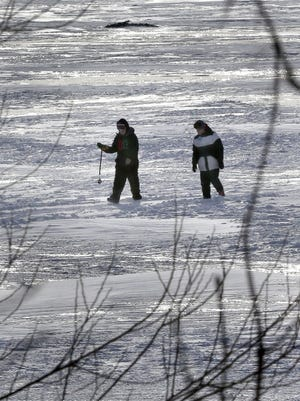 Tyler, left, and Teddy Simmons, both from Sherwood, walk across the ice on Lake Winnebago after scouting for a fishing spot on Feb. 2.