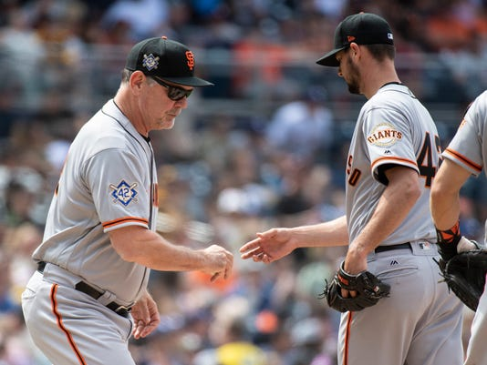 San Francisco Giants manager Bruce Bochy, left, removes starting pitcher Tyler Beede during the fourth inning of a baseball game against the San Diego Padres in San Diego, Sunday, April, 15, 2018. (AP Photo/Kyusung Gong)