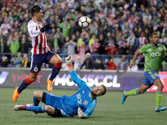 Seattle Sounders goalkeeper Stefan Frei, lower left, watches as Guadalajara forward Alan Pulido, left, jumps over him after Frei deflected a close-range shot by Pulido during the first half of a CONCACAF Champions League soccer match Wednesday, March 7, 2018, in Seattle. (AP Photo/Ted S. Warren)