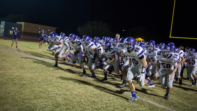 The Queen Creek football team runs out onto the field before the division VI quarterfinal playoff game November 14, 2014 in Goodyear.