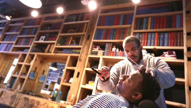 Personal groomer Nicholas Ashmon gives a haircut to Mark Teague at the Social Club Grooming Co. in Detroit on Wednesday, Feb. 11, 2015.