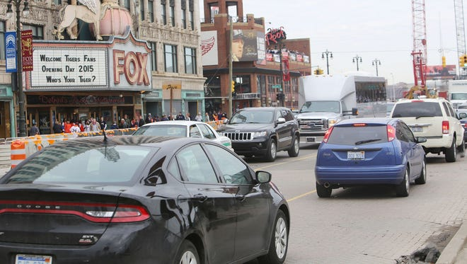 Traffic is  slow on Woodward Avenue in front of the Fox Theatre as cars maneuver around the construction of the M-1 Rail to the Detroit Tigers' Opening Day game at Comerica Park Monday, April 6, 2015.