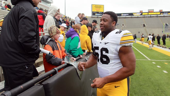 Iowa defensive lineman Faith Ekakitie signs autographs prior to the Hawkeyes' open spring game at Kinnick Stadium on Saturday, April 25, 2015.