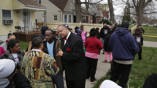 People gather by the home where a 19-year-old Detroiter was fatally shot by a federal agent at around 1 p.m. on the 9500 block of Evergreen near West Chicago in Detroit on Monday, April 27, 2015.