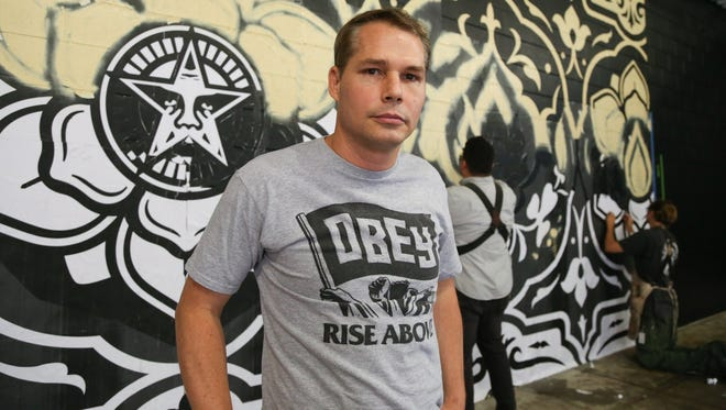 Artist Shepard Fairey works on a mural in The Belt alley in Detroit on Saturday, May 16, 2015.