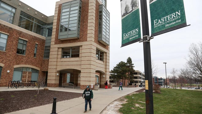 Students walk past the Halle Library on the Eastern Michigan University campus in Ypsilanti on Thursday, April 16, 2015.