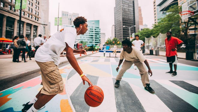 Elijah Favors, 17, of Romulus plays basketball against Jerry Johnson, 22, of Detroit on the courts at Campus Martius in downtown Detroit on Friday.