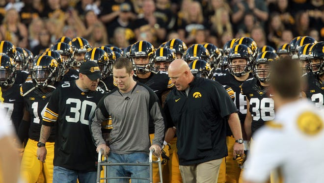 Former Colts linebacker Pat Angerer, left, helps former Iowa teammate Brett Greenwood as they lead the Hawkeyes onto the field.