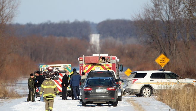 Emergency responders wait along Greencastle Avenue near the Iowa River in North Liberty after a man fell through the ice on Thursday, Dec. 31, 2015.