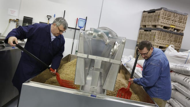 Laboda, right, and Bailey turn the malt in a tank at their facilities. Whereas the malting process is more mechanized at a large factory, the Motorcity operation involves plastic pitchforks and elbow grease.