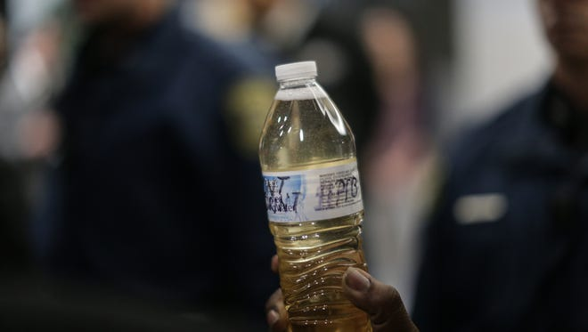 Julius Austin of the Change Agent Consortium holds a Flint resident's bottle of Flint water while occupying the lobby of the George W. Romney State Office Building on Jan. 14, 2016.
