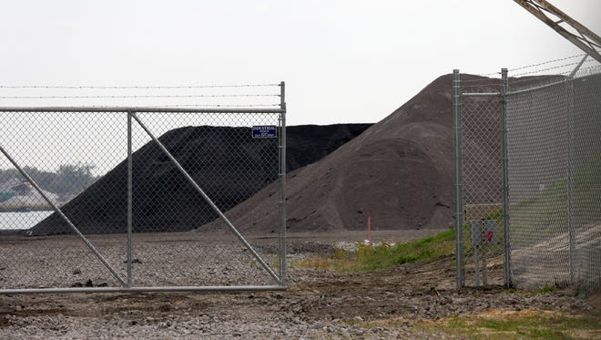 The pile in the background appears to be Petcoke. behind a fence at Jefferson and Junction on Thursday, October 8, 2015.