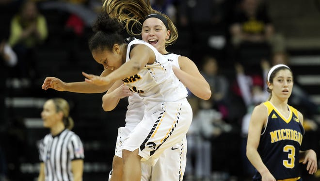 Iowa's Tania Davis and Alexa Kastanek celebrate as they head into a timeout during the Hawkeyes' game against Michigan at Carver-Hawkeye Arena on Thursday, Jan. 28, 2016.