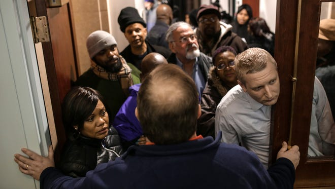 Immigration attorney Brad Thomson (right) 33, of Ann Arbor peeks his head into the room as residents and others are stopped from entering the Flint Water Class Action informational meeting due to it reaching capacity at the Northbank Center in Flint on Tuesday February 16, 2016.