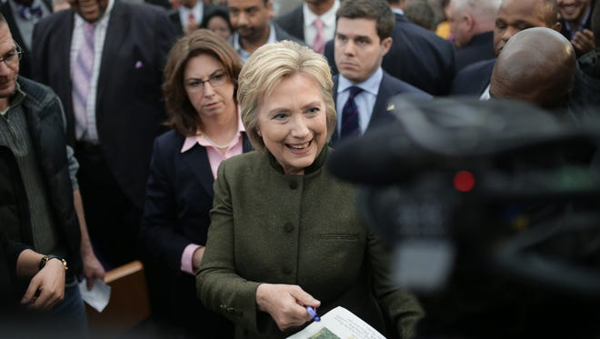Democratic presidential candidate Hillary Clinton signs autographs and talks with media after speaking to Flint residents at the House of Prayer Missionary Baptist Church in Flint on Sunday, Feb. 7, 2016.