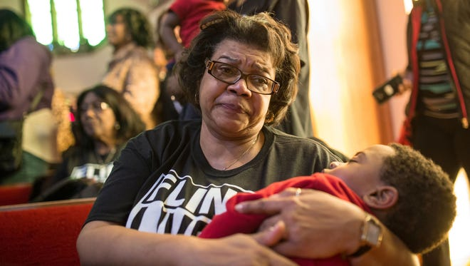Darlene Rogers of Flint sheds tears while holding holds her grandson Zavier Williams, 3, of Flint as a pastor talks about the effects of the lead in the water harming the children of Flint during a town hall meeting about the Flint water crisis on Monday February 1, 2016 at Flint Trinity Missionary Baptist Church.