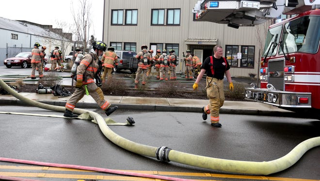 Firefighters work to put out a fire at a business and apartment building on Sunnyview Road near the Oregon State Fairgrounds in Salem on Tuesday, March 1, 2016. One man was rescued by firefighters and transferred to the hospital.