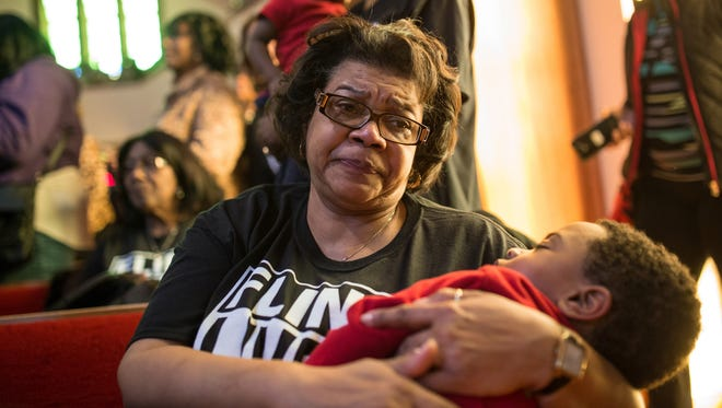 Darlene Rogers of Flint sheds tears while holding holds her grandson, Zavier Williams of Flint, as a pastor talks about the effects of the lead in the water harming the children in February 2016. Bills introduced last week include a pair of bills borne out of the Flint water crisis that would make it a felony to tamper with or alter evidence that is used in official reports.