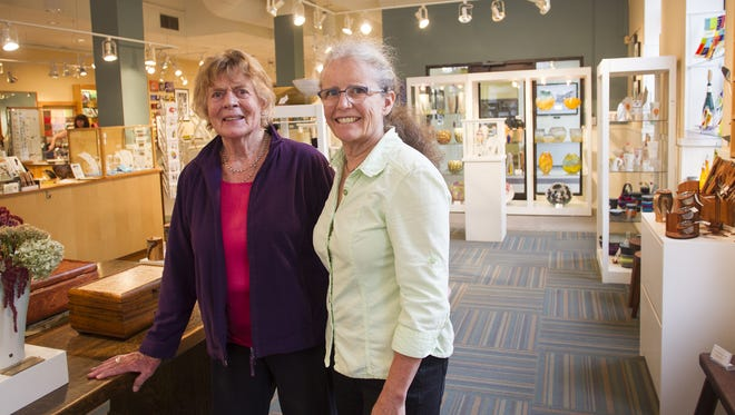 Iowa Artisans Gallery co-owners Christiane Knorr, left, and Astrid Bennett pose for a photo on Wednesday, Sept. 24, 2014.