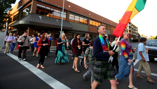 People walk during a vigil to honor those killed in the Orlando gay club mass shooting at the Salem Convention Center on Friday, June 17, 2016.