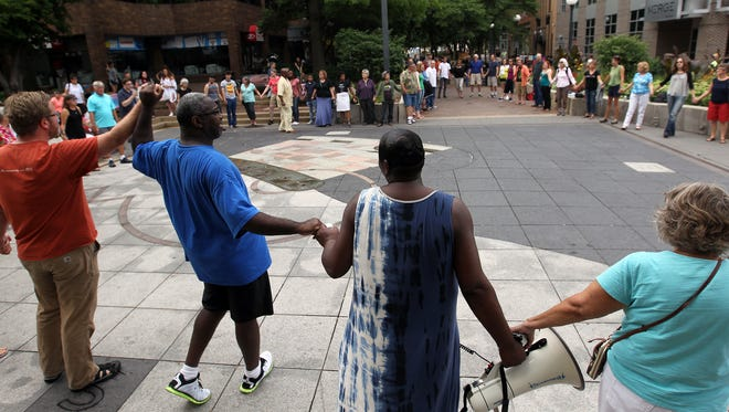 """Rockne Cole, from left, Anthony Currin, Royceann Porter and Karen Fox hold hands as community members sing, """"We Shall Overcome,"""" during a prayer vigil at the pedestrian mall on Sunday, July 10, 2016."""