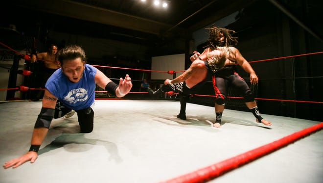"""Andrew Meade on stage as Fiji Widman wrestles Troy VanZant (left) and Tom VanZant (right) at the Wild Championship Wrestling Outlaws gym in downtown Indianapolis on July 1, 2016. Fiji works with his partner Shade Johnson """"Shad Satu"""" as a tag-team duo."""