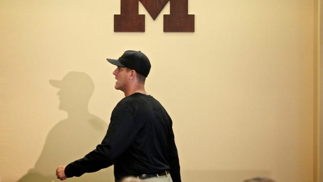 Michigan football coach Jim Harbaugh makes his way to the news conference to speak to reporters during U-M media day Sunday, August 7, 2016, at Michigan Stadium in Ann Arbor.