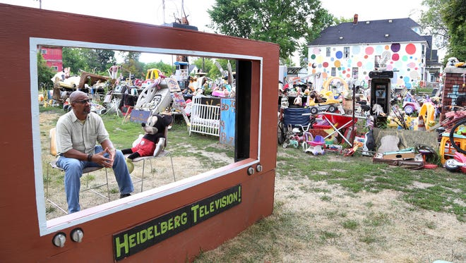 Tyree Guyton with a stuffed Mickey Mouse behind a make-shift TV screen at the Heidelberg art project inDetroit on Friday, August 12, 2016.