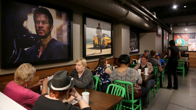 The first customers of the day to eat at Mark Wahlberg's Wahlburgers during the  grand opening in downtown Detroit's Greektown on Monday, August 15, 2016.
