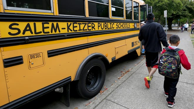 A student walks to school on the first day back for elementary schools at Grant Community School in Salem on Wednesday, Sept. 7, 2016.