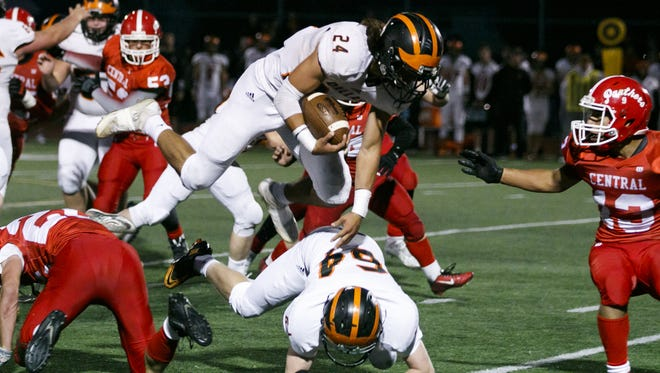 Dallas' Tanner Earhart (24) vaults over teammate Boe Bray (64) after colliding with Central's Isaiah Abraham (22) at a game on Friday, Sept. 30, 2016, at Central High Schoo in Independence.