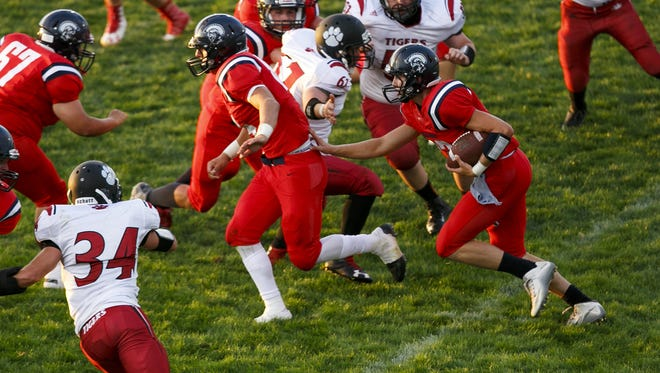 Kennedy quarterback Brett Traeger (12) carries the ball and tucks in behind running back Jack Suing (84) in the first quarter of the season-opening game against Clatskanie on Friday, Sept. 2, 2016, in Mt. Angel, Ore. The Kennedy Trojans defeated the Clatskanie Tigers 52 to 13.