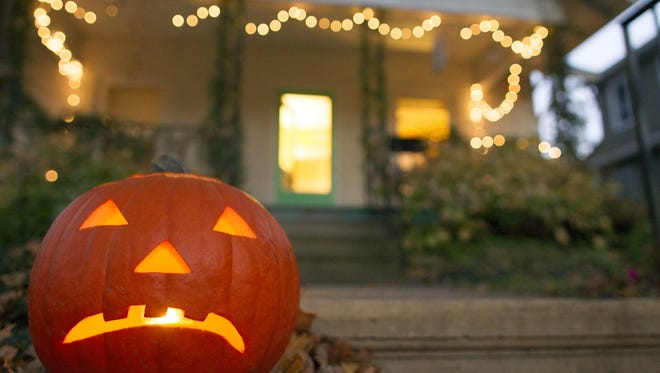 A carved pumpkin sits in front of a house on Friday, Oct. 31, 2014.  David Scrivner / Iowa City Press-Citizen