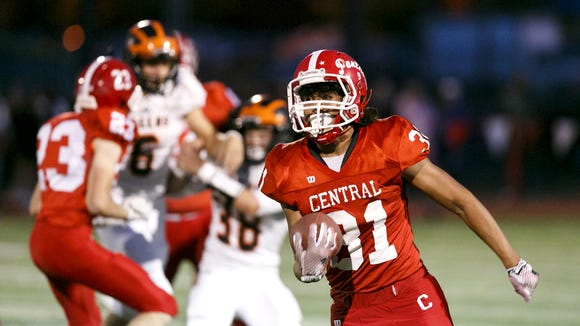 Central's AJ Morales (31) tucks in the ball and runs as teammates hold back the Dallas defence at a game on Friday, Sept. 30, 2016, at Central High School in Independence. Central won the game 21-20.