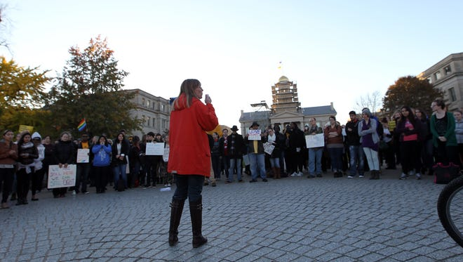 DeeAnn Grove of Coralville speaks to a large group of protesters in Iowa City on Friday, Nov. 11, 2016.