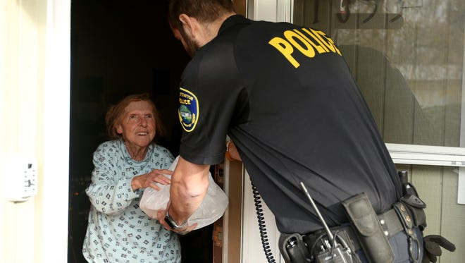Stayton police officer Robin Tepper delivers Thanksgiving meals to Betty Stephens in 2016 during the annual free community dinner.