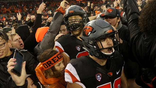 Oregon State fans rush the field following the Oregon vs. Oregon State Civil War football game at Oregon State University in Corvallis on Saturday, Nov. 26, 2016. The Beavers won the game 34-24.