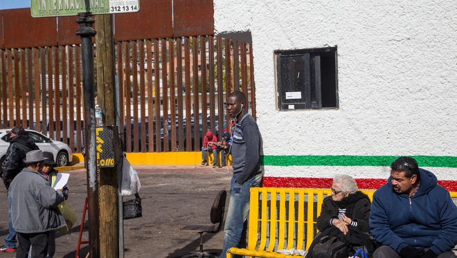 A Haitian migrant stands near the border fence in Nogales, Sonora, where the streets of Nogales, Arizona, can be seen through the slats. Between 200 and 250 Haitian migrants have arrived in this border city since October, hoping to cross through the port of entry into the U.S. without American visas.