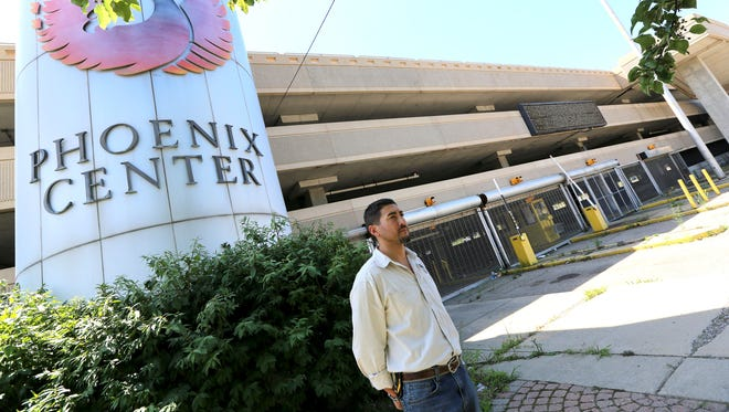 Michael Stephens, Facility Manager and Partner at Ottawa Towers, LLC stands in front of the sign to the Phoenix Center in Pontiac on July 27, 2015.