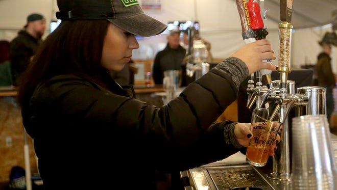 Taylor Laney pours a beer at the Winter Brewfest outisde the Oregon State Capitol in Salem on Friday, Feb. 3, 2017. The third annual event features more than 100 drinks on tap and continues through Saturday night.