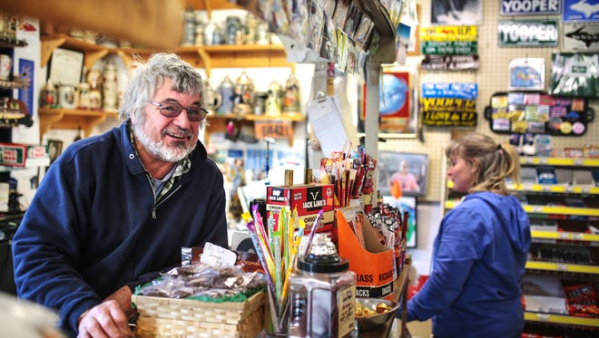 "Phil Pearce stands behind the counter at his store in Marquette. ""I want to be a nice guy,"" he said. ""That's what I want them to say when I die. He was a nice guy."""